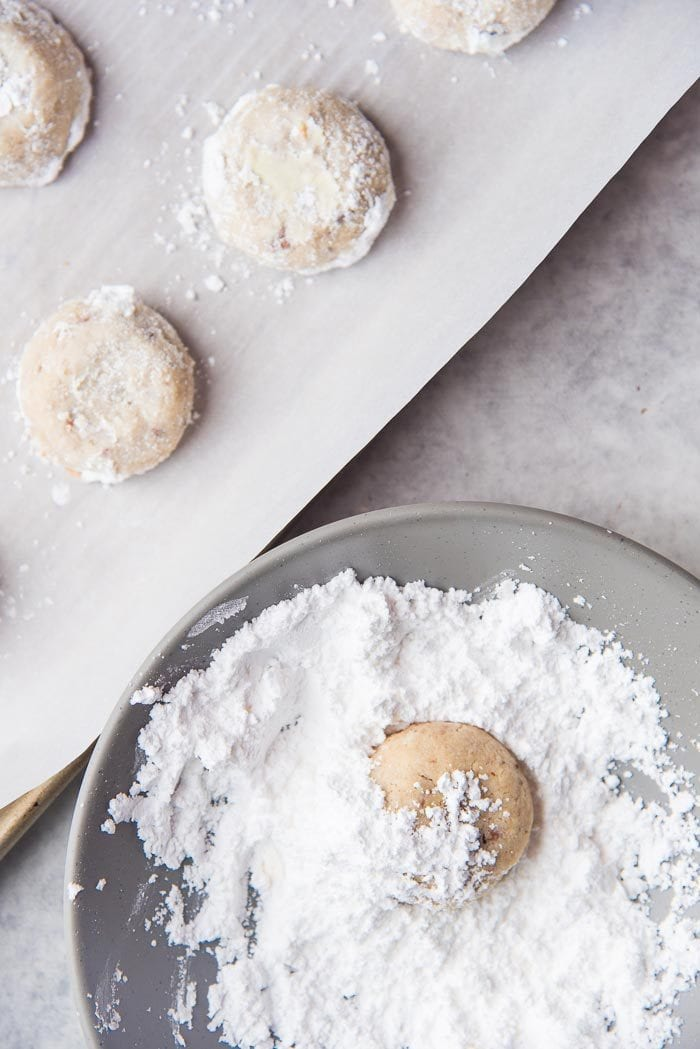 Freshly baked warm Mexican Wedding Cookies being coated with confectioners sugar in a bowl, and coated Mexican Wedding cookies on a baking tray