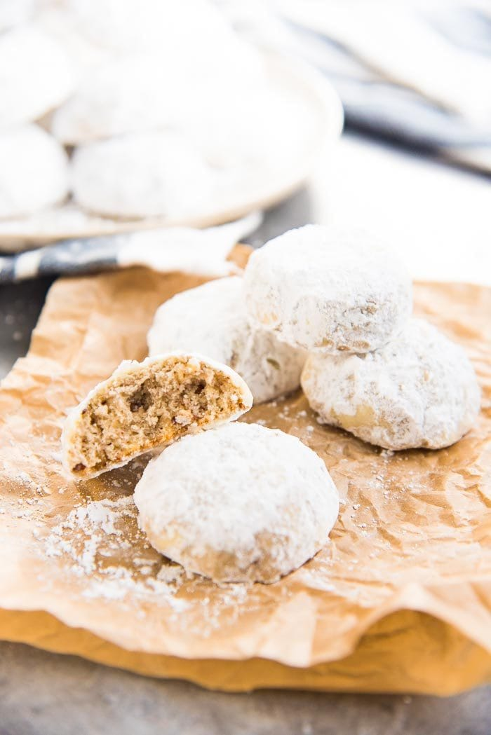 A few Mexican Wedding cookies placed on a brown paper, with a bite taken out of one cookie, and more cookies in the background.