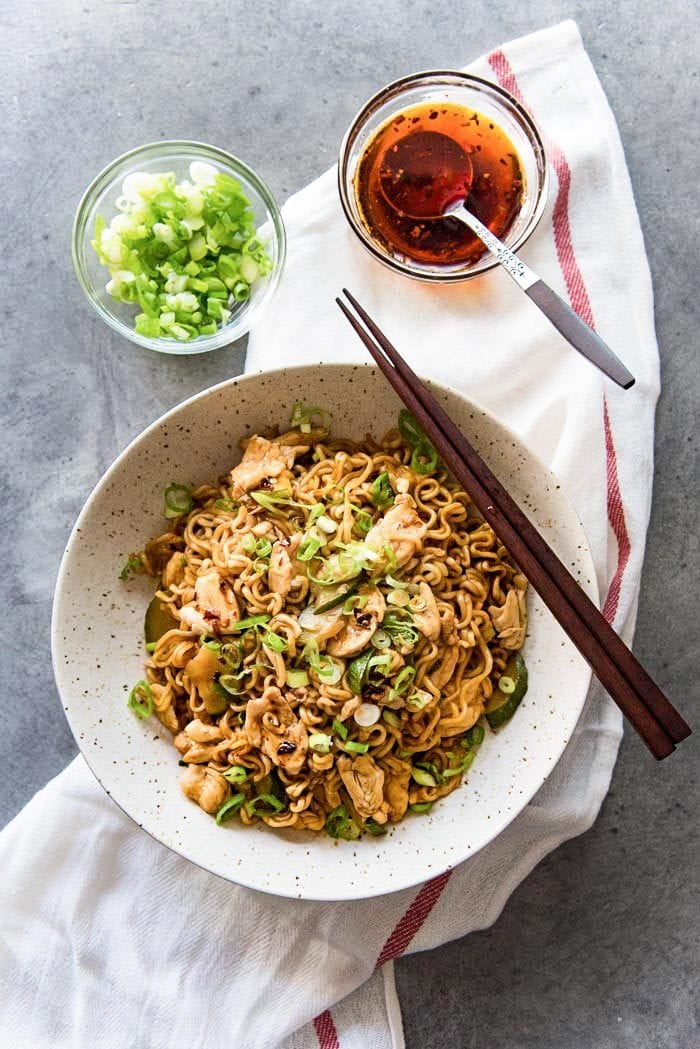 The Chicken ramen stir fry noodles are served in a bowl, with chopped green onions and chili sesame oil or regular sesame oil.