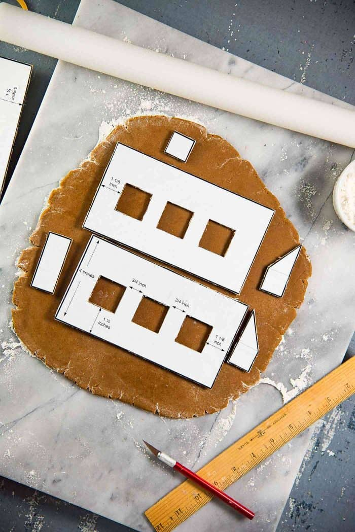 Gingerbread house template on rolled out gingerbread dough
