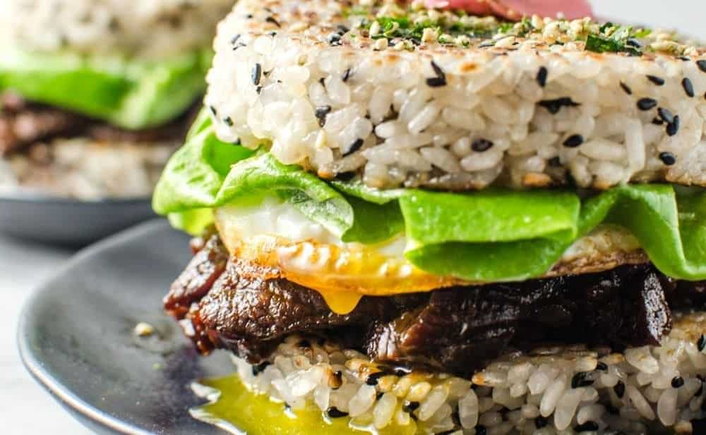"""Teriyaki Steak Sushi Burger - Whether you are outraged or intrigued, you cannot deny that this Steak Sushi Burger is insanely delicious! Delicious Teriyaki Glazed steak strips inside perfectly seasoned Sushi Rice """"Buns"""" and topped with a glorious Egg. Everything you love about Sushi, but as a burger! So easy to make. CLICK to get the recipe. REPIN for later. #TheFlavorBender"""