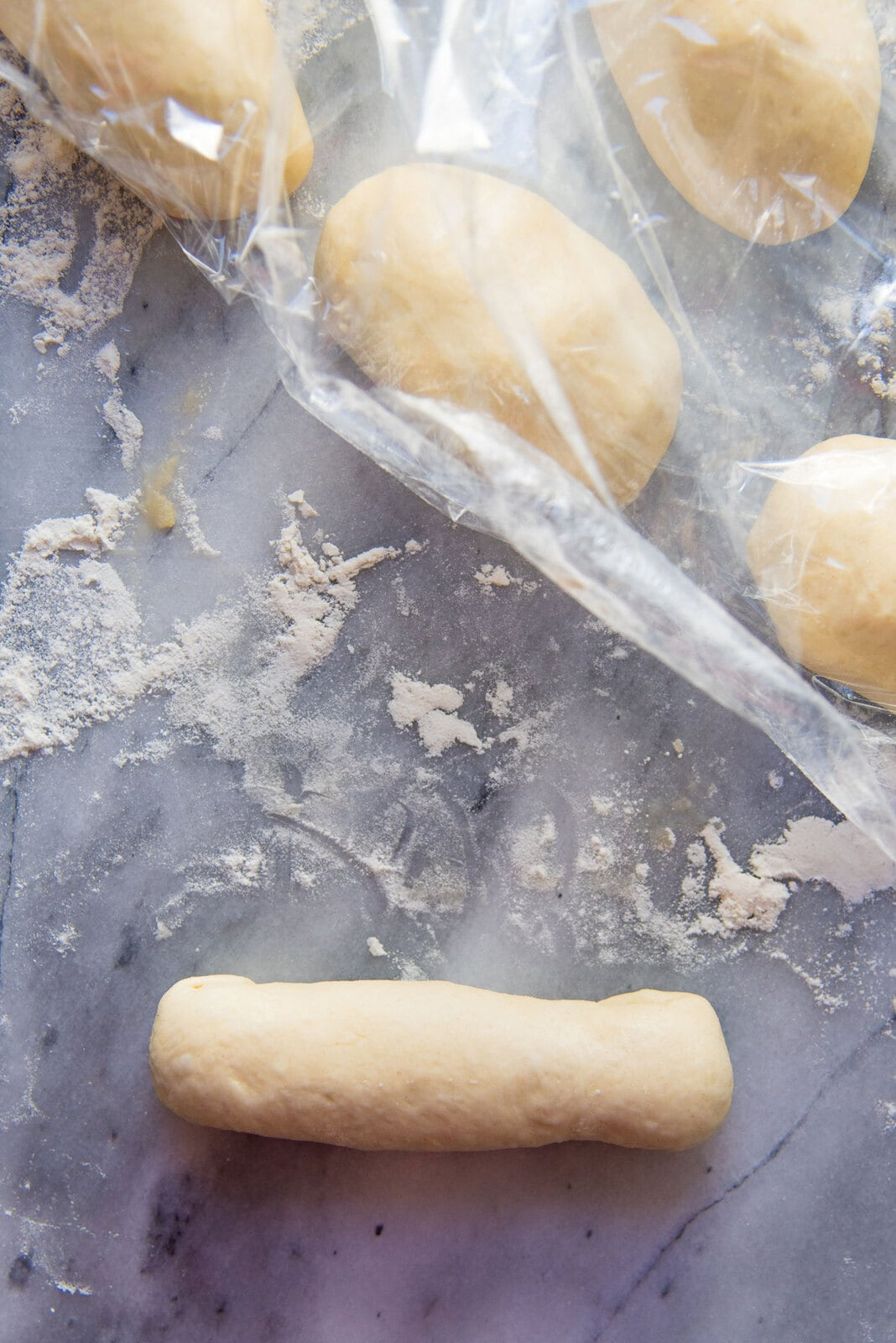 Easy Homemade Hot Dog Buns - The rolled and sealed hot dog bun is ready to be kept on the baking tray.
