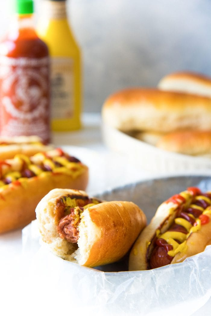 Easy Homemade Hot Dog Buns - A half eaten hot dog to show how soft and fluffy the hot dog buns are.