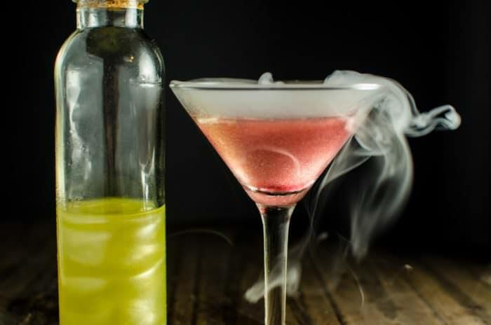 This Unicorn Blood Cocktail (A Peach and Raspberry Cocktail) is perfect for Halloween! Spooky, dark, but with a magical, fairy-tale like look! Made with homemade shimmery liqueur!