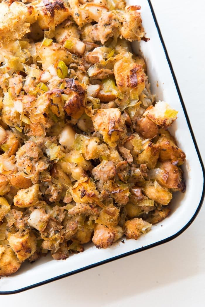 Sage Pear and Sausage stuffing in a baking tray, straight out of the oven. Caramelized pieces of pear and toasty bits of croutons on the surface, and sweet, juicy stuffing underneath.