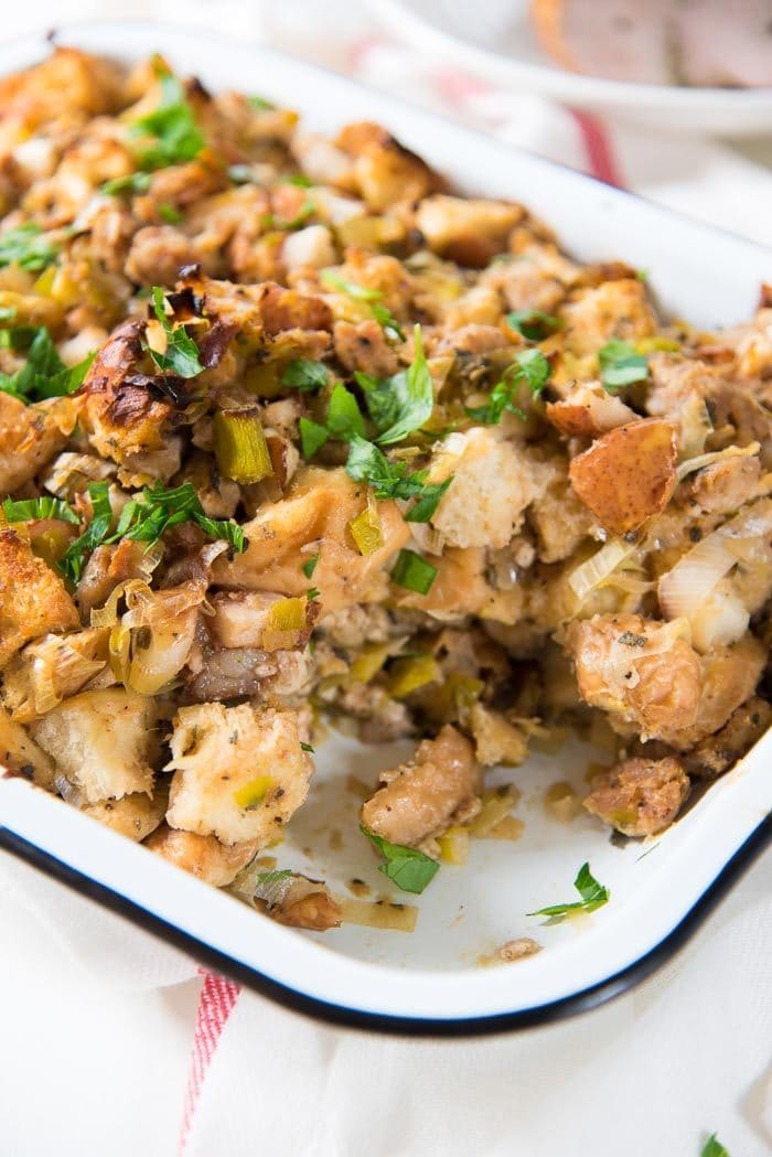 Sage Pear Sausage Stuffing in a white enamel baking dish, with the corner piece taken out.