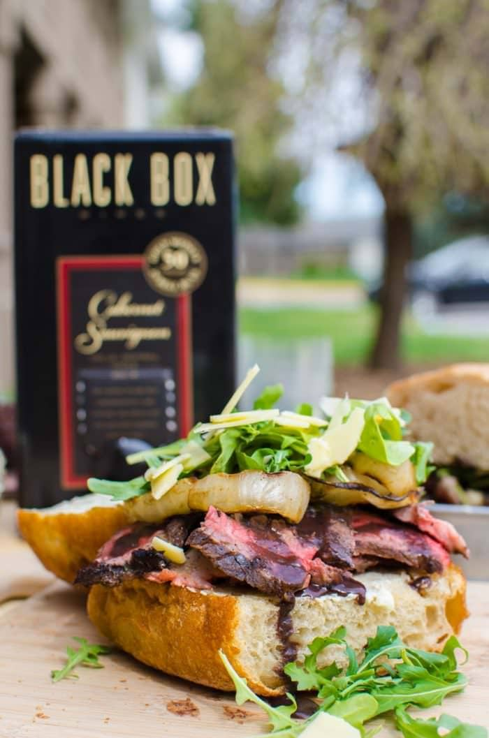 Red Wine marinated Steak Sandwiches with a Red wine Glaze, Grilled Onions, Arugula and Aged Cheddar. Red wine marinated, succulent, perfectly grilled steak, sliced and piled on toasted bread topped with a buttery red wine glaze! A Perfect Picnic Sandwich! REPIN to save. CLICK to get the recipe now. #TheFlavorBender #BlackBoxSummer