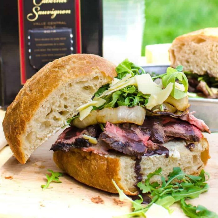 [Msg 4 21+] Red Wine marinated Steak Sandwiches with a Red wine Glaze, Grilled Onions, Arugula and Aged Cheddar. Red wine marinated, succulent, perfectly grilled steak, sliced and piled on toasted bread topped with a buttery red wine glaze! A Perfect Picnic Sandwich! REPIN to save. CLICK to get the recipe now. #TheFlavorBender #BlackBoxSummer [ad]