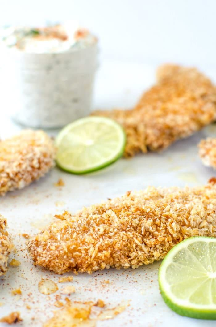Taco Spiced Crispy Baked Chicken Tenders - are absolutelyTHE BEST baked, crunchy chicken tenders, with a crispy and flavorful twist with a golden panko bread crumb coating and a taco spiced seasoning. Perfect with a Herb and lime Sour Cream dip! CLICK to get recipe. REPIN for later! #TheFlavorBender