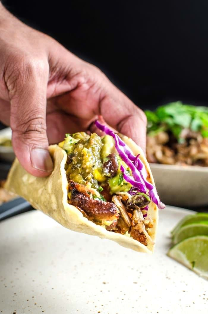 Pork Carnitas Tacos with Mango Black Bean Salsa and Salsa Verde - Make Taco night extra special with thisMoist, juicy, tender pork carnitas with crisp brown edges, and a fresh, colorful, fruity mango black bean salsa, topped with roasted tomatillo salsa verde on slightly toasted tortillas. REPIN to save. CLICK to get the recipe. #TheFlavorBender