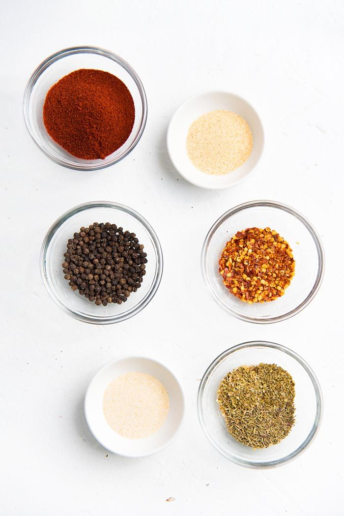 Spices that are used to make Homemade Cajun seasoning, in separate bowls.
