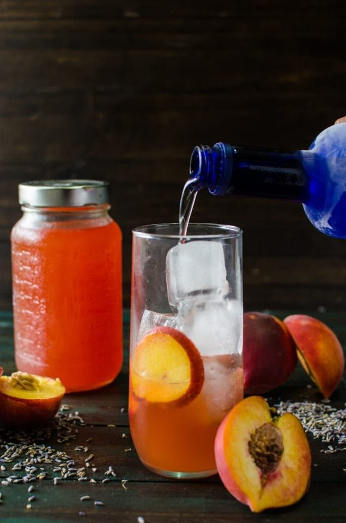 Lavender Peach Shrub Syrup - This sweet, fruity, tangy, floral Lavender Peach Shrub Syrup is simple to make and is a great way to use up bruised, overripe peaches. Mix with ice cold water for a refreshing, non-alcoholic summer drink, or with some vodka or tequila for a delicious cocktail, or with some champagne for a wonderful mimosa!