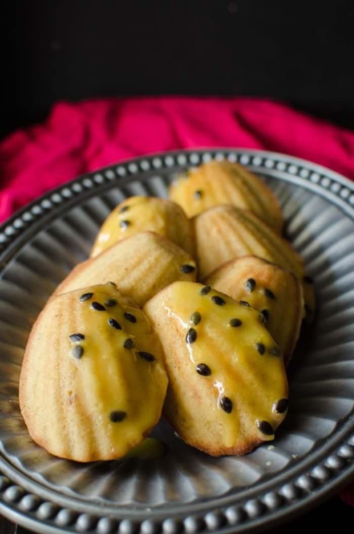 Brown Butter Madeleines with Passion fruit Glaze - Get your holiday baking off to an amazing start with these beautifully baked Madeleines with a soft, sponge cake center and crisp, browned edges and a delicious nutty brown buttery flavor and a sweet and tangy passion fruit glaze! PLUS tips to get PERFECT Madeleines every time!