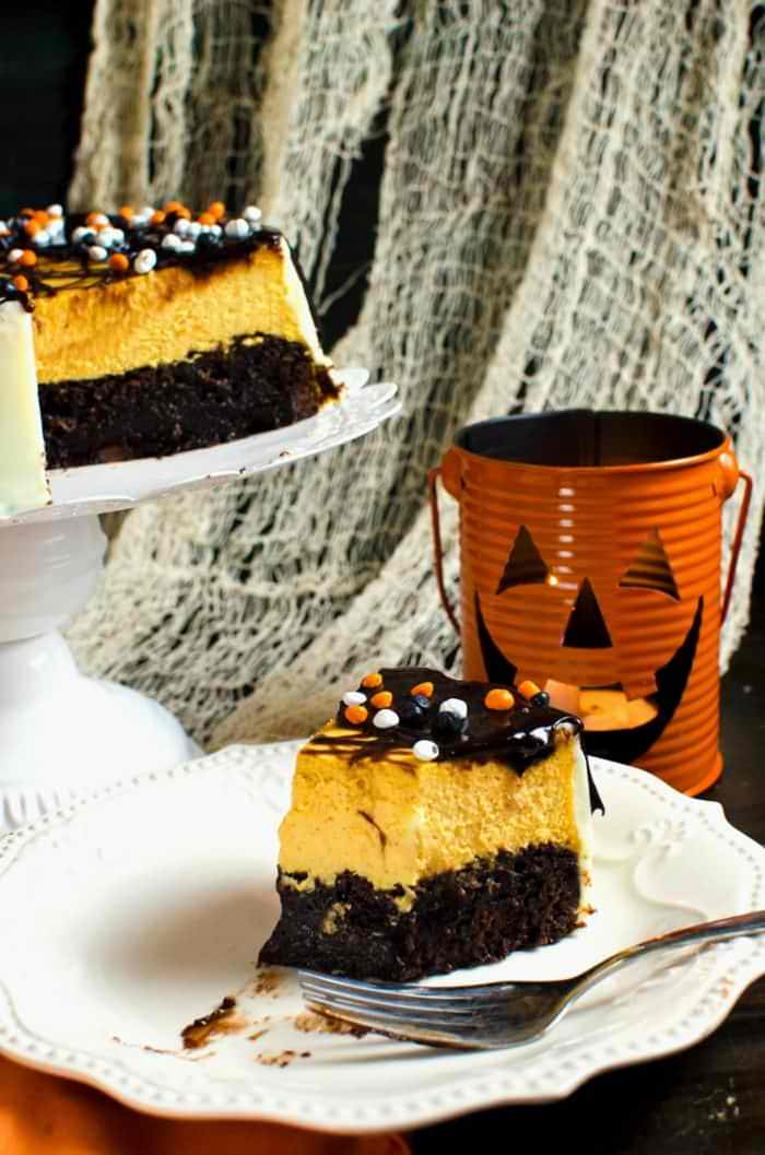 Brownie Bottom Pumpkin Cheesecake With Chocolate Fudge Sauce - A delicious combination of Fudgy brownies and creamy Pumpkin cheesecake in one dessert! Dress it up for Halloween or keep it simple to celebrate Thanksgiving or Fall. A great twist on Brownie Bottom Cheesecake with Fall flavors and Halloween cheer!