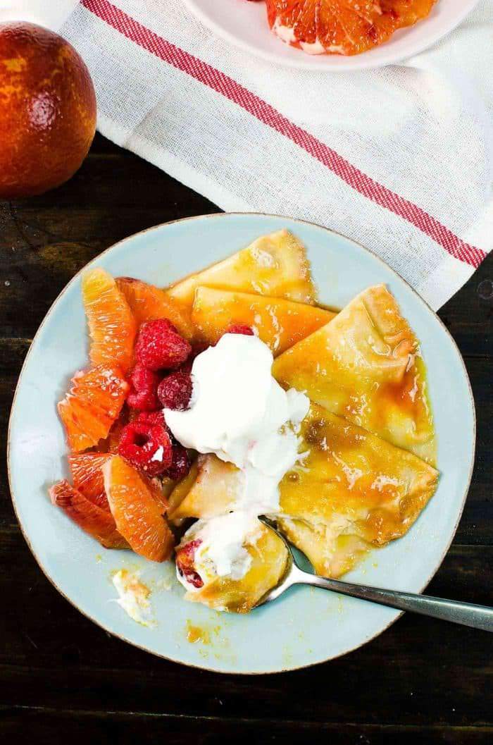 Blood Orange Crepe Suzette For Two - Pillowy soft crepes, coated in a blood orange infused rich, buttery, citrusy caramelized syrup and served with extra blood orange segments, raspberries and a dollop of whipped cream.This is the perfect date-night worthy, simple yet spectacular dessert!