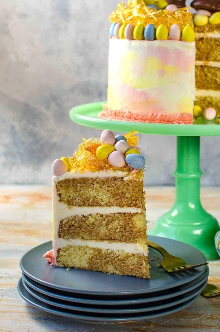 Chai and Vanilla Cake with soft, fluffy Vanilla Buttercream frosting - A spectacular swirled Easter cake with a gorgeous pastel watercolor effect, decorated with Easter eggs, chocolate bunnies and a caramelized nest on top! A sunny, happy and outrageously delicious cake to celebrate all of life's special occasions and nostalgic memories!