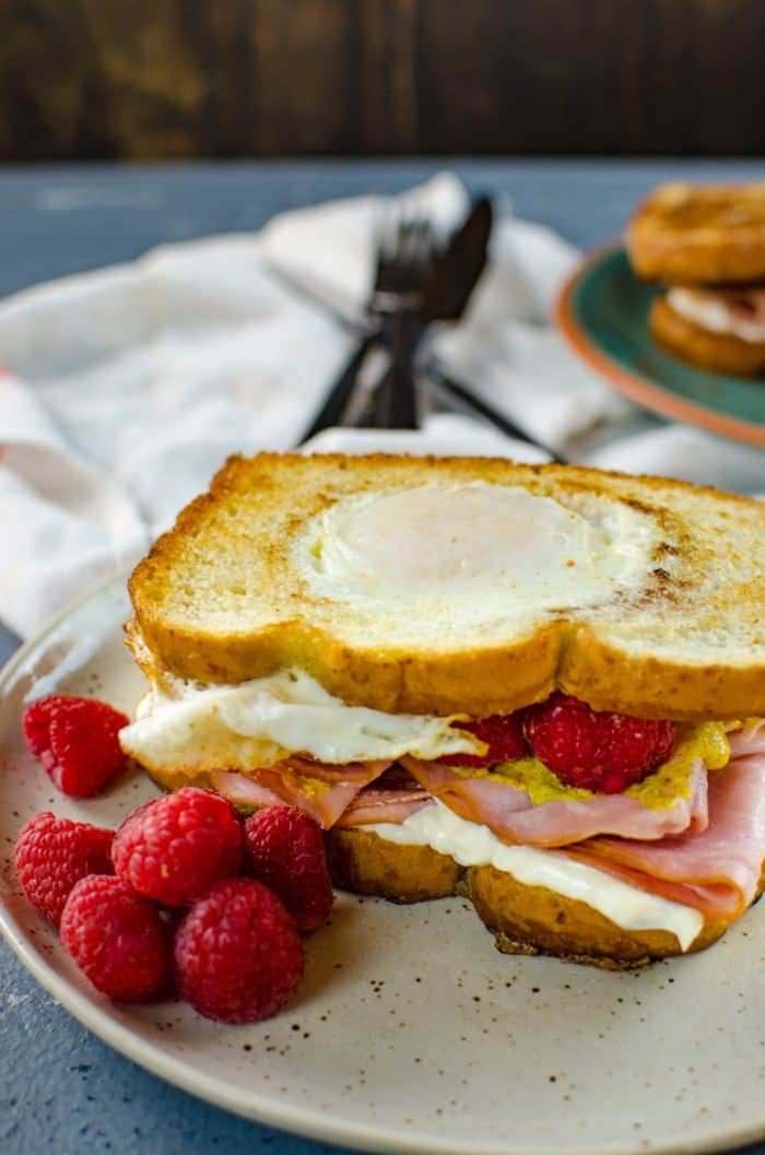 Raspberry, Ham and Egg sandwich - This is the definition of a happy sandwich! Creamy with a touch of sweetness, fruity freshness and an egg cooked right into a slice of toast. A twist on a Monte Cristo Sandwich with just 6 ingredients.