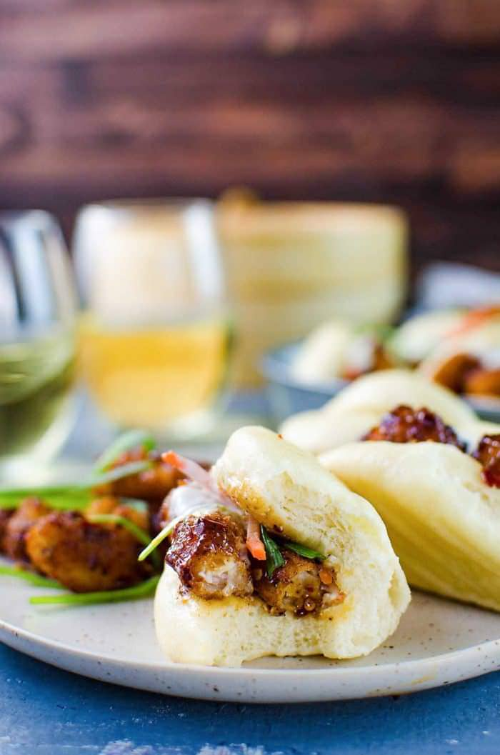 Deliciously easy, Spicy Asian Popcorn Shrimp Bao - Perfect forbusy weeknights. Restaurant-quality, flavor-packed meal in just 15 - 20 minutes with crispy oven-baked popcorn shrimp, tossed in a spicy Asian sauce and then served with steamed Chinese bao buns (or slider buns) with crunchy carrots and spring onions!