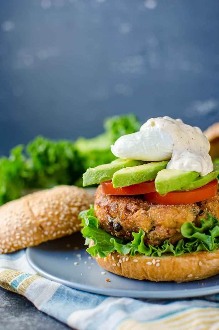 Crispy Tuna Burger with Lemon and Capers - A delicious burger topped with a spiced aioli tartar sauce, tomatoes, avocado and an egg. A close up of the flaky tuna buger, with chunks of delicious tuna!