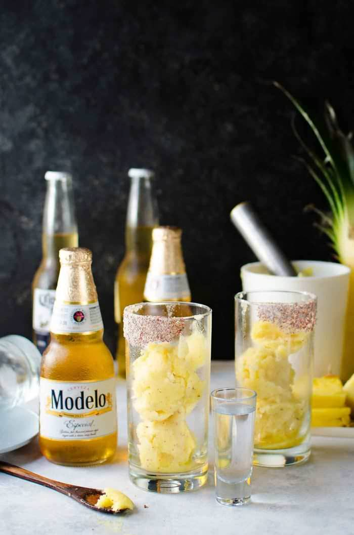 Frozen Pink Peppercorn Pineapple Margarita Shandy - The ULTIMATE summer cocktail, perfect for Cinco de Mayo! Pineapple and Pink Peppercorn sorbet in glasses with salted rims! Just top up with tequila and beer!