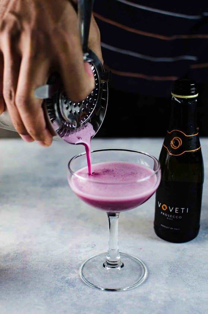 Sparkling Blueberry elderflower sour - This prosecco cocktail is a cross between a mimosa, and a whiskey sour. Strain the Blueberry Elderflower Whiskey sour into champagne glasses.