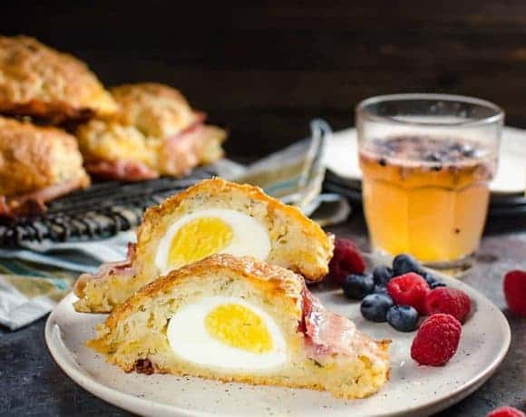 Bacon wrapped Egg Stuffed Breakfast Biscuits (Breakfast Scones) - Cheesy and herby buttermilk biscuits that are delightfully soft in the middle and extra flaky on the outside, and stuffed with a perfectly cooked egg and wrapped with bacon for good measure. Perfect for Brunch.