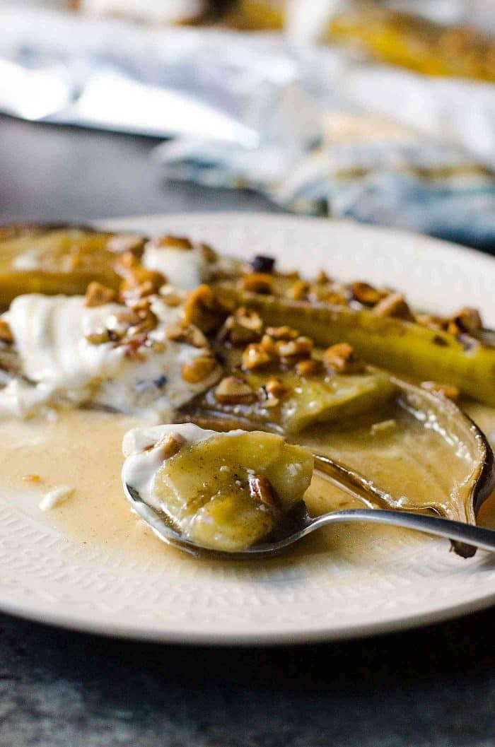 Easy Brown Butter Baked Bananas Foster - A simple dessert with comforting flavors for Fall and Winter! Sweet Caramelized Bananas in a Rum butter sauce topped with toasted hazelnuts and pecans and Vanilla yogurt. Can be made for a crowd or just for two!