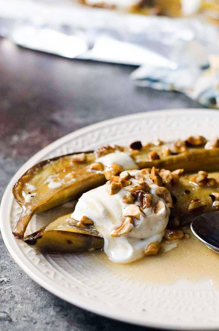 Easy Brown Butter Baked Bananas Foster - Sweet Caramelized Bananas in a Rum butter sauce. Served with toasted hazelnuts, pecans and vanilla yogurt!