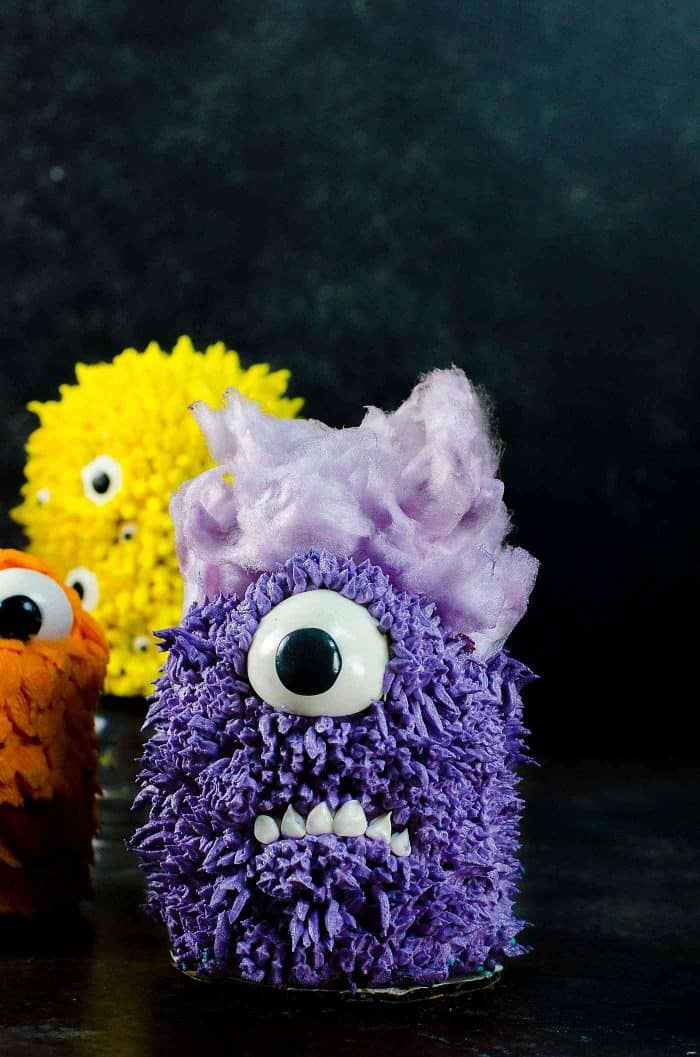 Purple Minion Monster - Inspired by the minion. with Purple fur buttercream and candyfloss hair. Mini Monster Cakes (Halloween Cakes) - A cake recipe for fudgy Chocolate Sheet cake and a full step by step tutorial to make 5 mini monster cakes that are perfect for Halloween Parties or Monster themed parties.