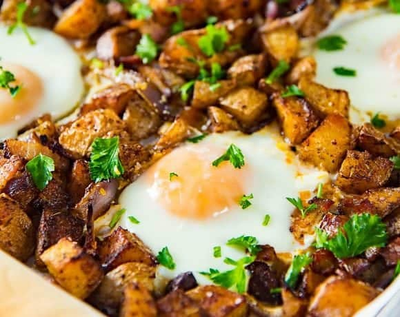 Sheet pan Breakfast Potatoes with Bacon and Eggs - This oven roasted breakfast potatoes and eggs with crispy bacon bits, are all cooked in the same sheet pan so you can enjoy your weekend mornings without standing over the stove.