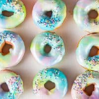Mini Rainbow Donuts with a unicorn Glaze- Colorful and gorgeous, fried donuts made with rainbow colored dough and coated with a rippled unicorn glaze.