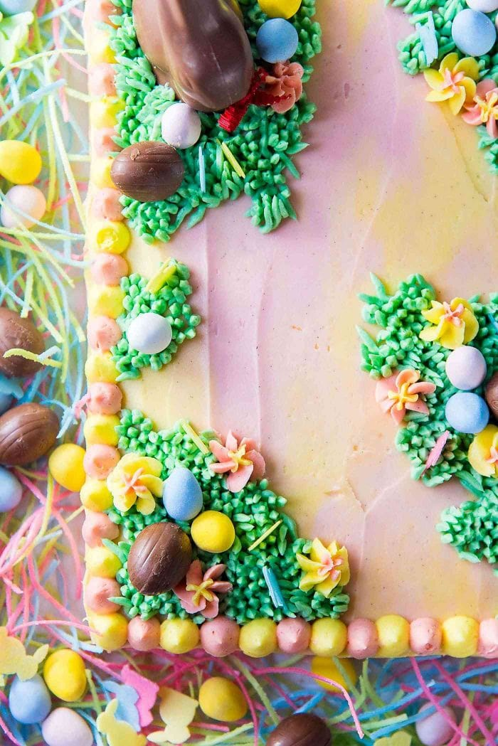 Pastel Easter Cake - A swirled pastel cake with pastel buttercream, decorated with patches of buttercream grass, buttercream flowers, and chocolate Easter eggs.