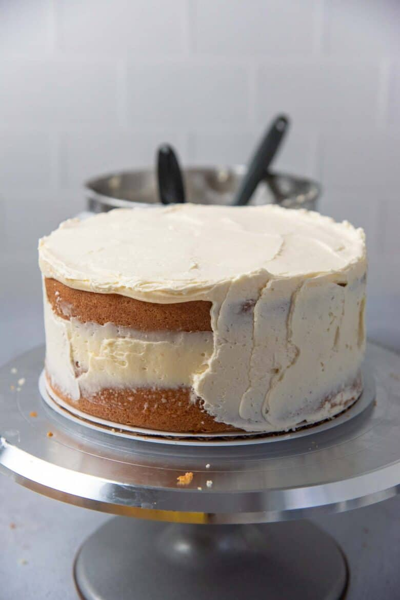 A crumb coating covering half of the cake