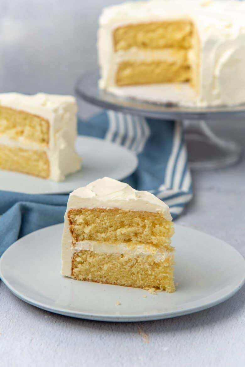 A slice of the best vanilla cake on a plate with other cake slices in the background