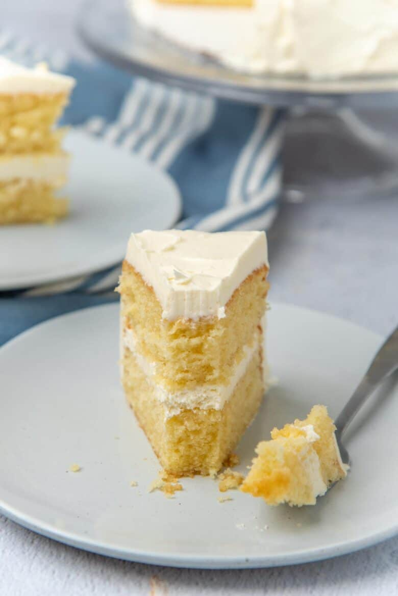 A slice of cake with a piece taken off using a fork that is placed next to the cake slice
