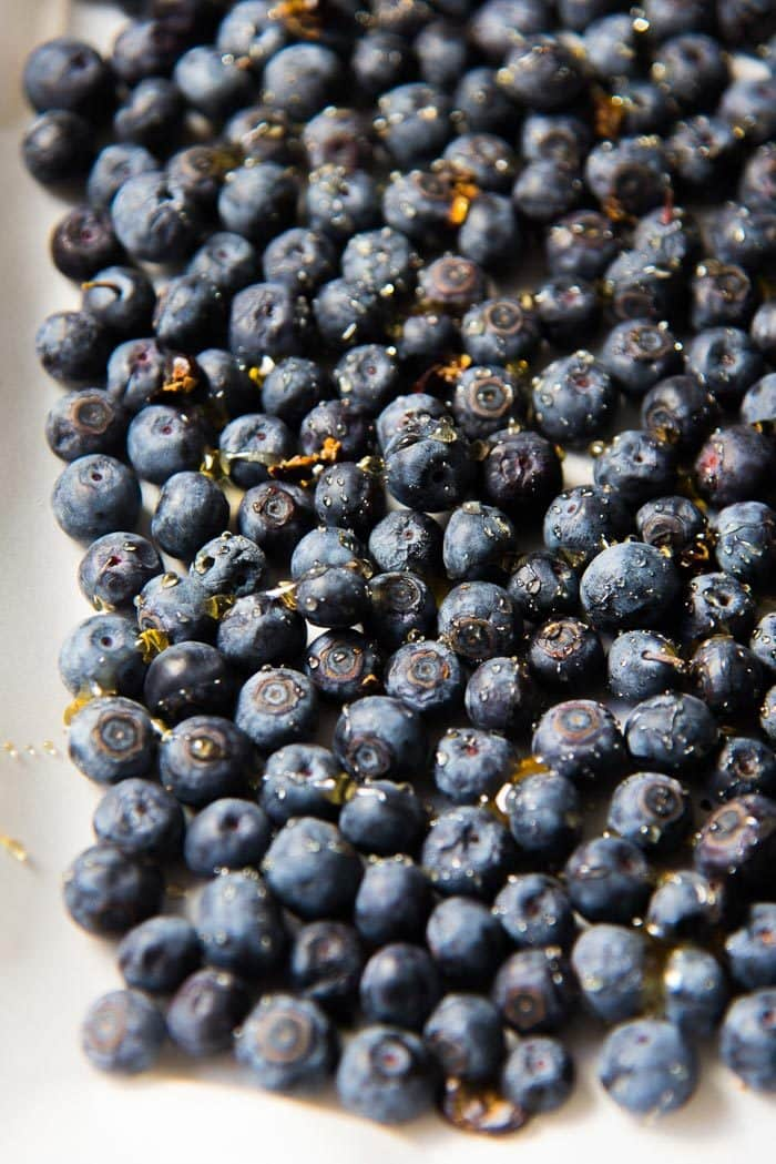 An image of the fresh blueberries on a parchment paper baking tray, with a drizzle of honey.