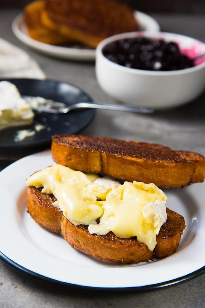 Two slices of caramelized cinnamon toast on a white plate. One slice is topped with melted brie, and the other slice is propped behind the first toast. Roasted Blueberries are in a bowl behind the plate.