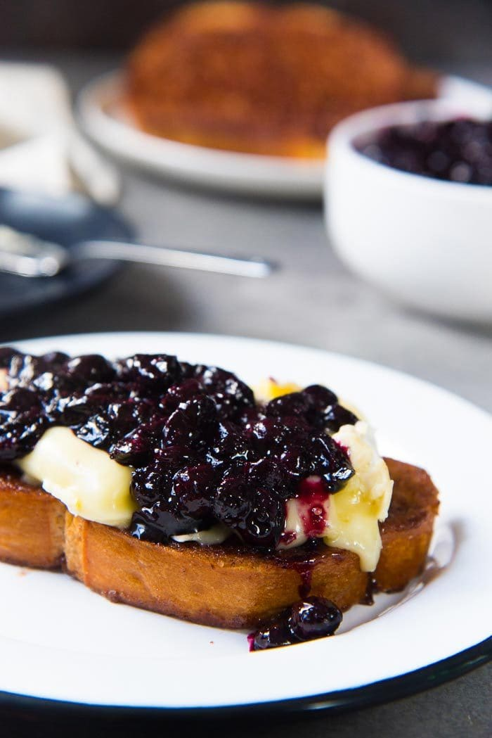 One slice of cinnamon toast topped with melted brie and a generous amount of roasted blueberry compote ontop, on a white plate.