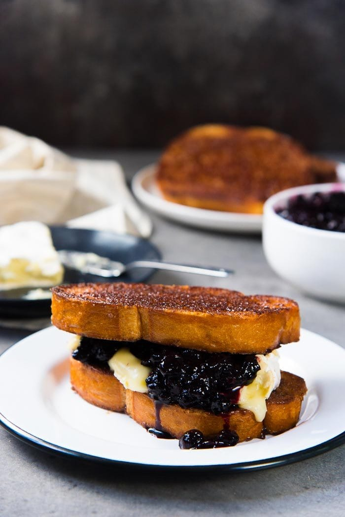 Two slices of buttery cinnamon toast as a sandwich with melted brie and blueberry compote in the middle, on a white plate.