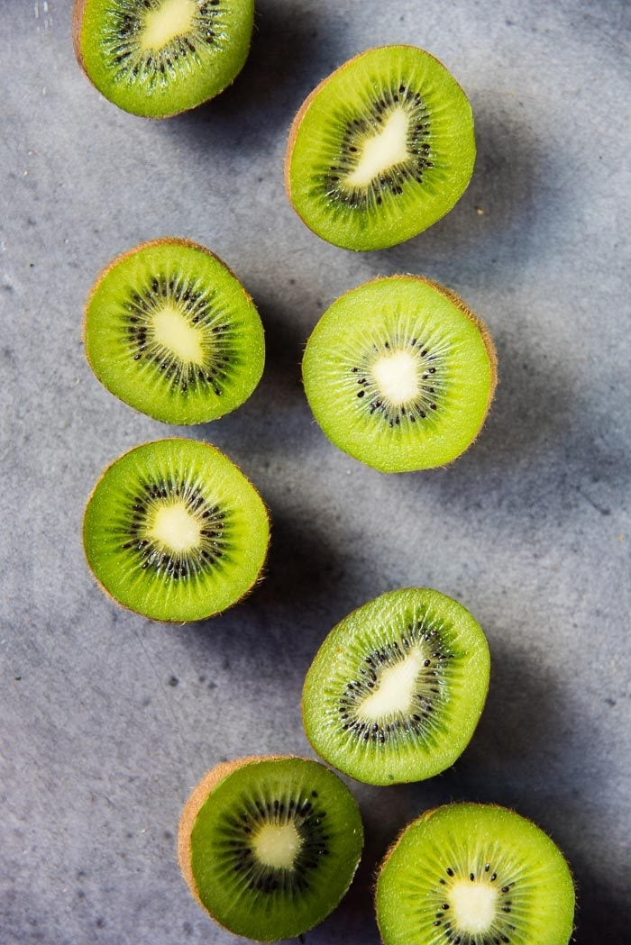 Halved kiwifruits on a gray table. A delicious summer fruit that's a perfect snack.