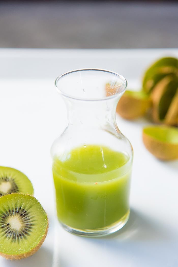 Kiwi fruit juice in a glass bottle next to halved kiwi fruits.