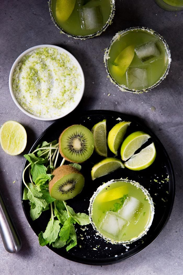An overhead view of Kiwi Mint Margarita. One cocktail on a black plate next to a bunch of mint, sliced kiwi fruits and lime wedges. A small plate of lime salt and 2 more cocktails in the background.