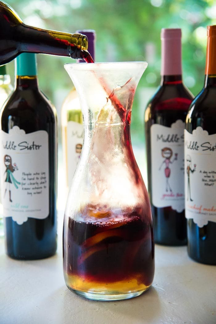 A bottle of red wine, being poured into a carafe with manderin slices, mandarin juice, gin and elderflower syrup.