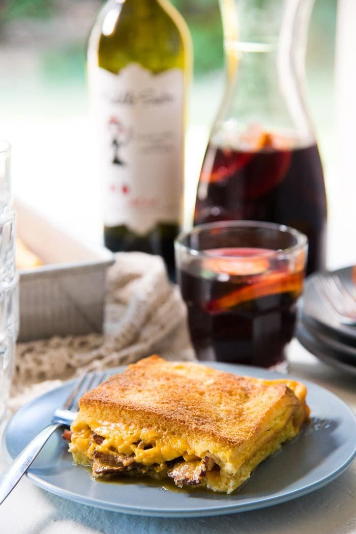 A slice of bacon cheese grilled Cheese sandwich casserole on a blue plate, with pieces of bacon and cheese peeking through the edges. With a glass of red wine an elderflower sangria in the background, with a bottle of wine, more plates, and the baking dish in the background.