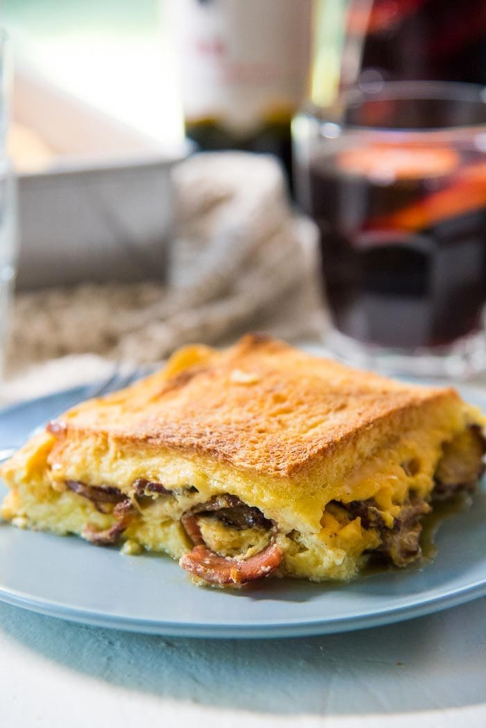 A close up of a slice of bacon cheese grilled Cheese sandwich casserole on a blue plate, with pieces of bacon and cheese peeking through the edges.