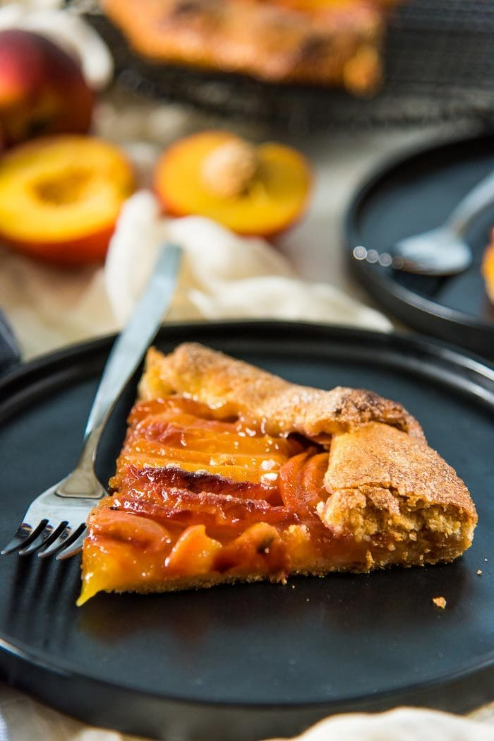 A close up of the peach galette slice, with the juicy peach filling and the golden all butter pie crust, on a black plate, with fresh peaches in the background.