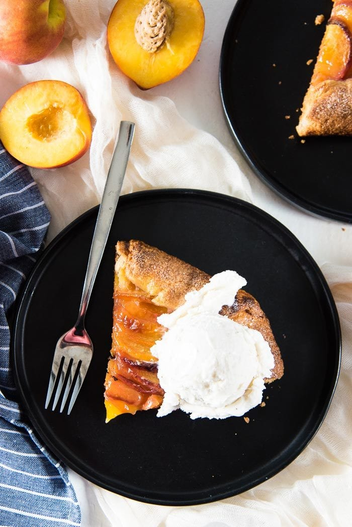 An overhead photo of a slice of peach galette with a scoop of ice cream on top.