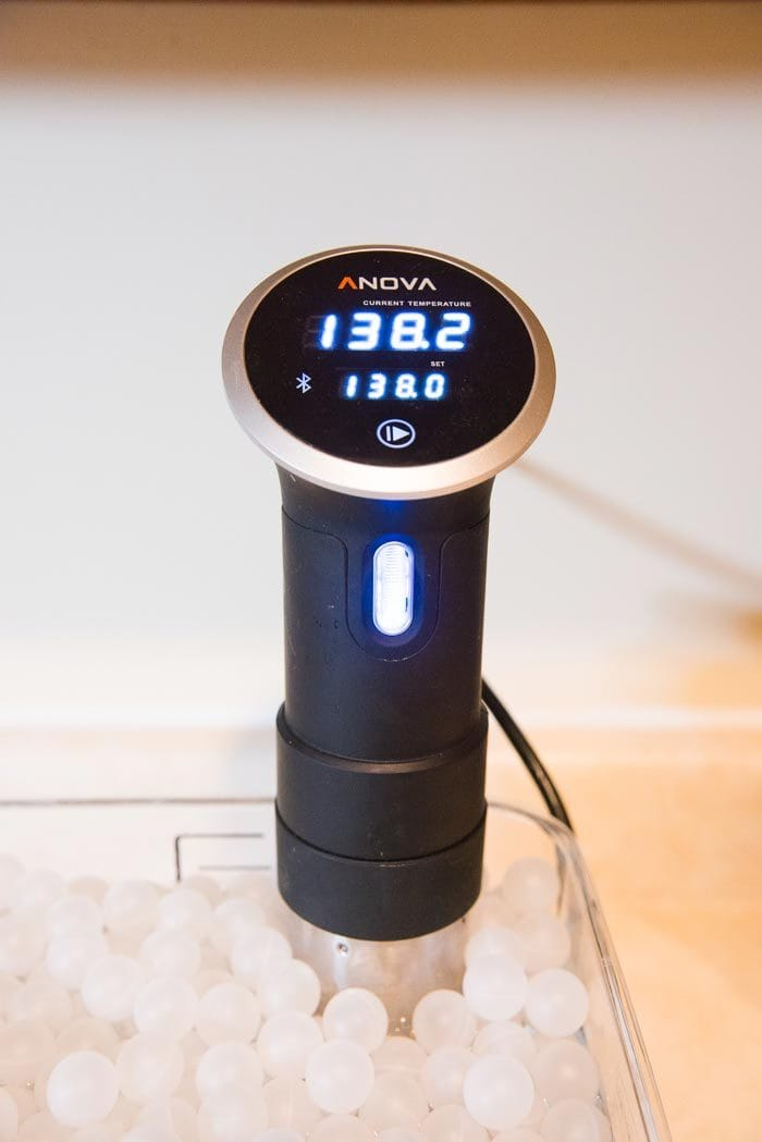A sous-vide anova cooker in a water bath, with the temperature set at 138°F.