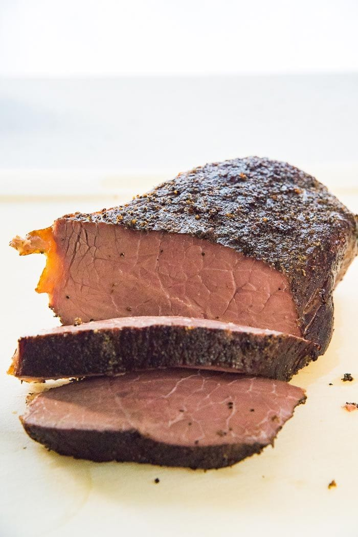 A medium cooked Sous-vide rump roast (bottom round roast), with two slices cut, on a white cutting board.