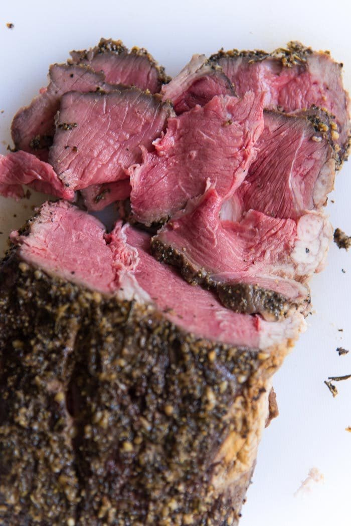 An overhead photo of slow roasted rare beef roast with a rosemary garlic spice crust, and thinly sliced beef slices next to it.